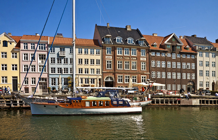 Panoramic view of Nyhavn, famous touristic landmark of Copenhagen and waterfront built in 17th-century flanked by antique houses with bright colorful facades.