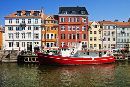 flanked: Pictorial view of Nyhavn, famous touristic landmark of Copenhagen, built in 17th-century as harbor flanked by antique houses with bright colorful facades. Editorial