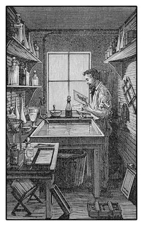 darkroom: Photographer working in a darkroom, processing light sensitive photographic materials for print