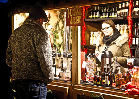 liqueurs: Munich, Germany - festive atmosphere at Harras Christmas market, kiosk selling a selection of liqueurs and schnaps Editorial