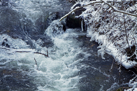 winter rural landscape, running waters and icicles with frozen leaves on the riverbank