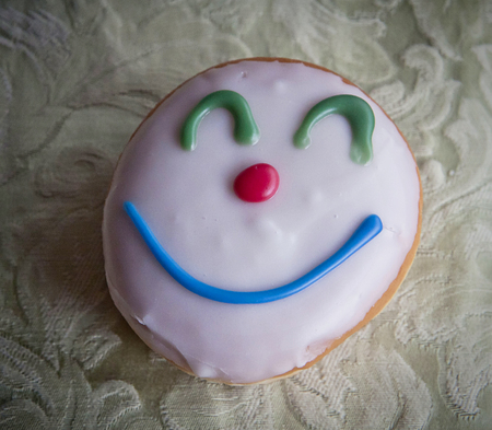 Carnival doughnut with glazed cream and clown face decoration Stock Photo - 72831097