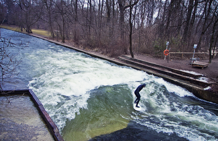 Munich, surfer riding the artificial wave on the Eisbach, small river across the Englischer Garten, in a freezing February morning Stock Photo - 73736086