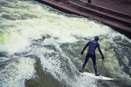 Munich, surfer riding the artificial wave on the Eisbach, small river across the Englischer Garten, in a freezing February morning Stock Photo - 73736087