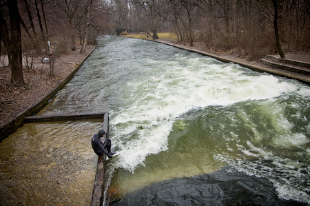 Munich, English Garden - solitary surfer prepares to surf the artificial wave of the Eisbach river in a freezing February morning with temperature below 0 (32 F) Editorial