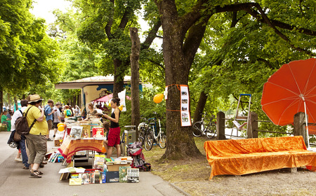 Book flea market with beautiful warm weather at the Isar river promenade in Munich center: used books to read, browse and buy under the trees with a rive-gauche-like charming feeling