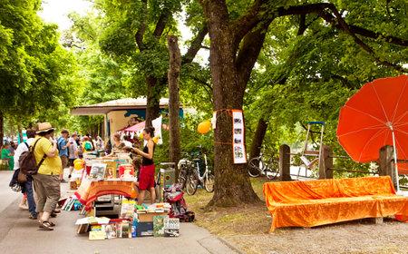 Buchen Sie Flohmarkt mit wunderschönem warmen Wetter an der Isarpromenade im Münchner Zentrum: Gebrauchtes Bücher zum Lesen, Durchsuchen und Kaufen unter den Bäumen mit einem rustikalen, bezaubernden Gefühl Standard-Bild - 81527459
