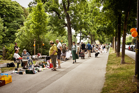 collectible: Book flea market with beautiful warm weather at the Isar river promenade in Munich center: used books to read, browse and buy under the trees with a rive-gauche-like charming feeling