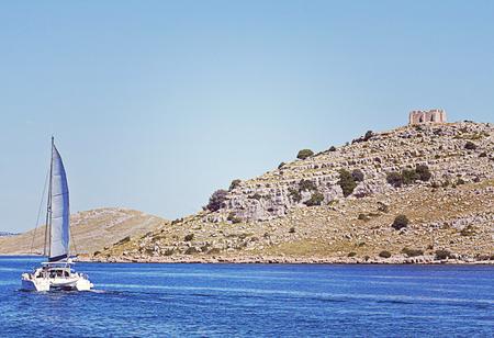 Catamaran cruises along an island of Kornati archipelago with an antique fortress on top. Stock Photo