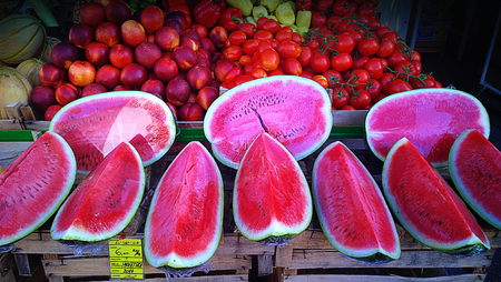 red shiny and ripe water melon slices, peaches and tomatoes on sell at market stall Stock Photo