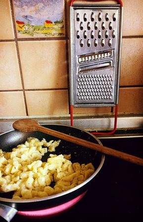 Stir-frying spaetzle, German soft egg noodles, in the kitchen on the cooking plate Stock Photo