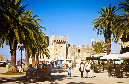 CROATIA, TROGIR - Tourists walk on Trogir sea promenade flanked by lush palms and cafe bars, with the view of the Kamerlengo medieval castle Editorial