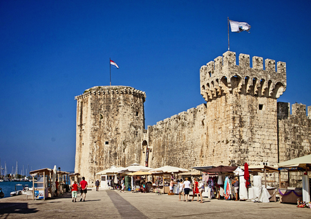 TROGIR, CROATIA - tourists shop souvenirs and stroll on the sea promenade near Kamerlengo castle, medieval fortress built from Venice around 1500 to defend the town of Trogir from Turk  invasions Editorial