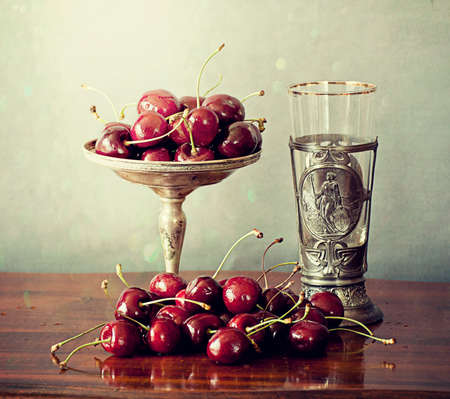 Vintage silver objects and ripe red cherries on a wooden table