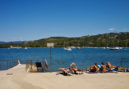 Slovenia, Saint Bartholomew bay right at the Italian border, people sun-bathing in front of the blue sea of mid-August