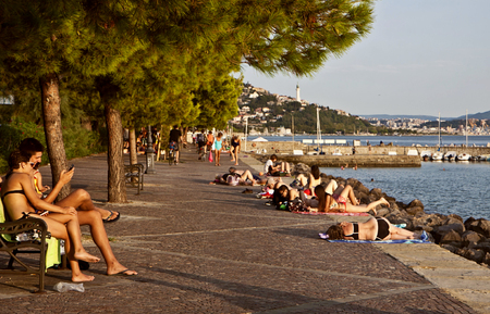 Trieste, Barcola sea promenade at sunset, people enjoy the summer warm weather