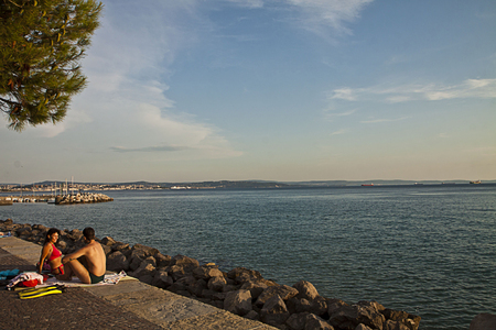 Trieste, Barcola sea promenade at sunset, couple enjoy the summer warm weather Editorial