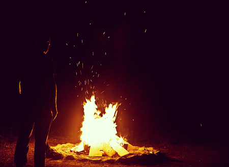 Camping vacation outdoors, bonfire in the night, bright with sparkles and man silhouette