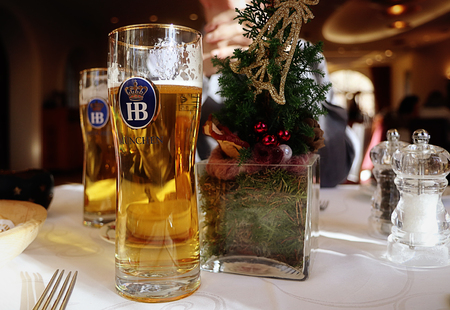 holiday decorated table and two glass of Bavarian HB famous beer Editorial