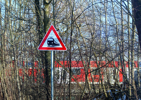 railroad level crossing sign on rural road and train traveling across Stock Photo