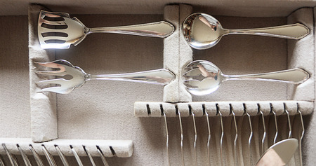 Beautiful vintage silver server flatware in a case, detail of decorated spoons and forks in antique design