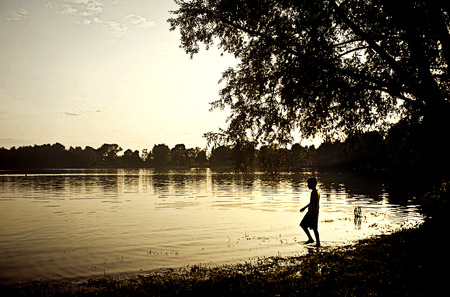 Silhouette of a boy entering in the lake waters at dusk