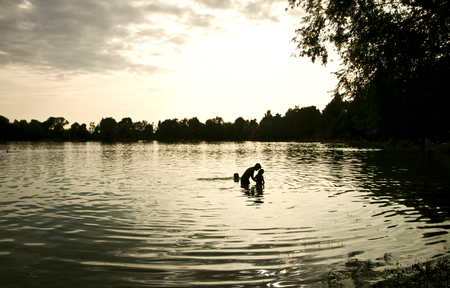 Silhouette of a kids swimming and playing in the lake waters at dusk