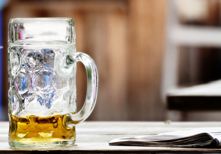 Beer glass abandoned on a desk with a newspaper, soft focus, blurred background