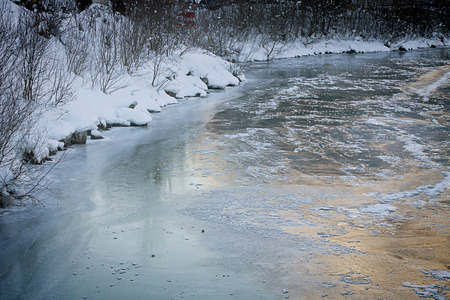 Beautiful reflection of the mountains at sunset on the iced and glazed surface of a river Stock Photo