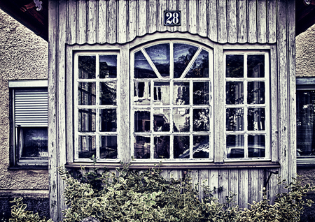 Rural abandoned house with wooden bowwindow