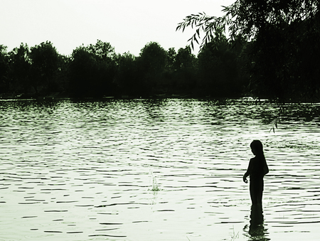 Young girl throws a stone in the lake waters at evening
