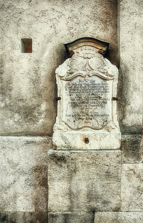 Antique tombstone, year 1749, with carved inscription in old German, in a niche of a church wall Stock Photo