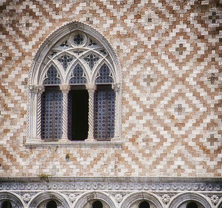 Venice, palazzo Ducale: detail of tripled arcade window and facade decoration with alternate red marble and white stone brick paving, soft focus Фото со стока