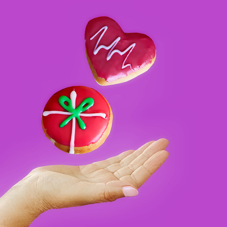 Delicious red glazed doughnuts jumping in hand on purple background