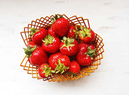 Wicker basket with ripe and red strawberries top view