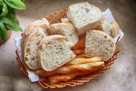Basket with Italian ciabatta bread with black olives and German salzstangen on the table