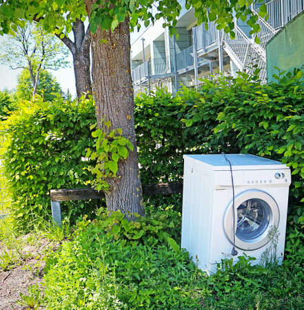 A washing machine dumped as garbage and abandoned on the sidewalk, sharply contrasting with the green environment Stock Photo