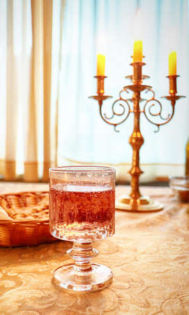 Glass of sparkling rose' wine on a damask cloth on the dinner table at candle light, soft focus