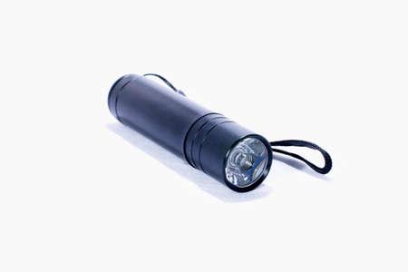 Steel flashlight on black surface