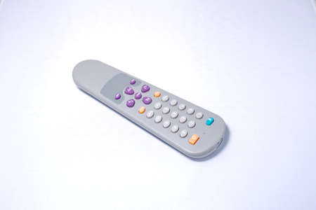 Remote control changing channels while watching TV in background Stock Photo - 13087097