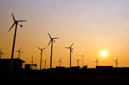 Clean energy wind turbine silhouettes at sunset, at Chonburi Thailand photo