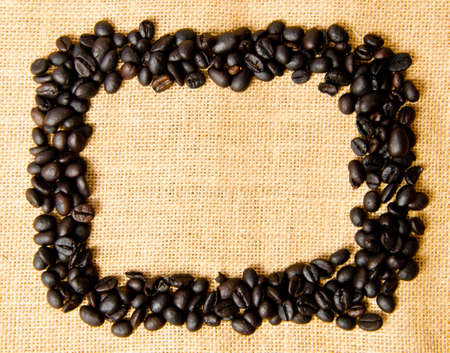 Shape of frame made of coffee grains on sack background photo
