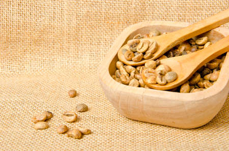 gunny: Coffee beans on wooden spoons and cup , on sack Stock Photo