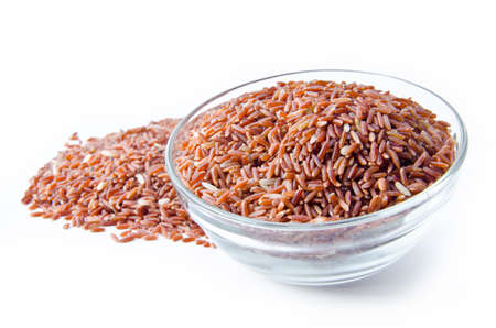 Bowl of raw brown rice on white background