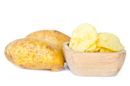 Potato chips in a wooden bowl and fresh potatoes on white background photo