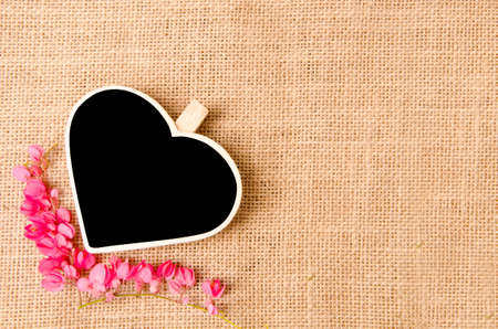 Black wood clip heart shape and flower on sack background photo
