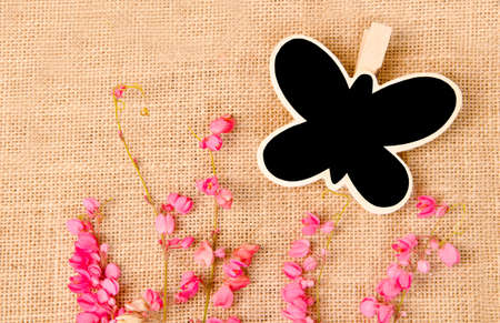 Black wood clip and flower on sack background photo