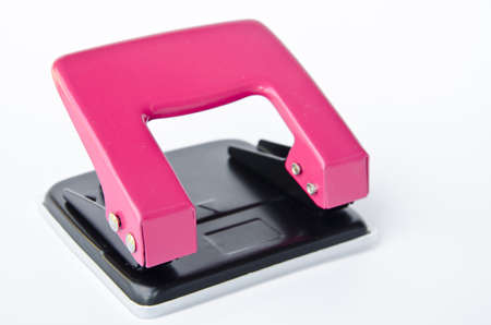 punch press: pink office paper hole puncher on white background