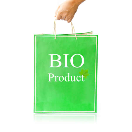 Hand hold green paper shopping bag on reflect white floor. BIO product photo