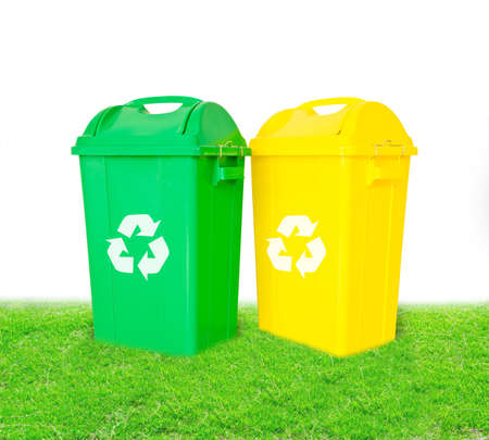 Green and yellow plastic trash recycling container with recycle sign ecology concept, on grass background.